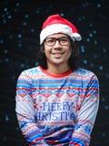 穿圣诞老人帽子和圣诞快乐毛线衣的亚裔人 图库摄影