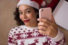 穿圣诞老人帽子和圣诞节毛线衣的微笑的女孩使用聪明 免版税库存照片
