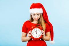 穿圣诞老人服装的哀伤的妇女拿着时钟 图库摄影