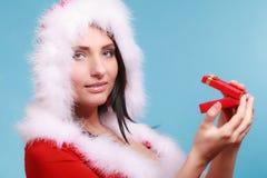 穿圣诞老人服装的妇女拿着在蓝色的礼物盒 免版税库存图片
