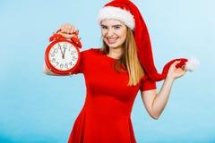 穿圣诞老人服装的妇女拿着时钟 库存照片