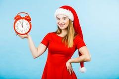 穿圣诞老人服装的妇女拿着时钟 图库摄影
