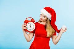 穿圣诞老人服装的妇女拿着时钟 免版税库存图片