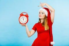 穿圣诞老人服装的妇女拿着时钟 库存图片