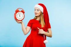 穿圣诞老人服装的妇女拿着时钟 免版税库存照片