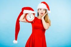 穿圣诞老人服装的妇女拿着时钟 免版税图库摄影