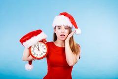 穿圣诞老人服装的愉快的妇女拿着时钟 库存照片