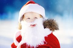 穿圣诞老人服装的滑稽的小男孩在冬天多雪的公园 免版税库存照片