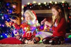 穿圣诞节睡衣的愉快的妹使用由一个壁炉在自圣诞前夕的一个舒适黑暗的客厅 库存图片