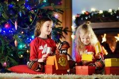 穿圣诞节睡衣的愉快的妹使用由一个壁炉在自圣诞前夕的一个舒适黑暗的客厅 免版税库存照片