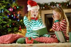 穿圣诞节睡衣的愉快的妹打开礼物盒由一个壁炉在自圣诞前夕的一个舒适黑暗的客厅 免版税图库摄影