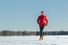 穿在冬天训练的连续人红色防护运动服户外 免版税图库摄影