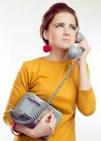 穿在减速火箭的样式的少妇黄色礼服与老电话 库存照片