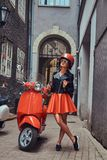 穿在太阳镜和盔甲的性感的白肤金发的女孩时髦的衣裳,站立在有两的一条老狭窄的街道上减速火箭 免版税库存照片