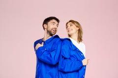 穿在浅粉红色的背景的滑稽的年轻美好的夫妇一件夹克 免版税库存图片