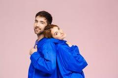 穿在浅粉红色的背景的滑稽的年轻美好的夫妇一件夹克 库存照片