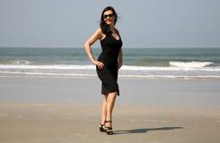 穿在海滩的可爱的女孩黑礼服 免版税图库摄影