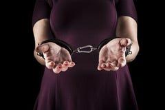 穿在皮革的服从妇女一件紫色礼服扣上手铐  免版税库存图片