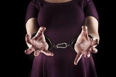 穿在皮革的服从妇女一件紫色礼服扣上手铐  库存照片