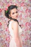 穿在花背景的美丽的妇女一件新娘礼服 库存图片