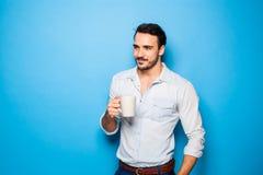 穿在蓝色背景的英俊的成人人便衣 免版税库存照片