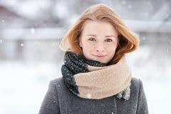 穿在被弄脏的冬天背景的秀丽画象自然看起来的年轻可爱的红头发人女孩被编织的围巾灰色外套 免版税图库摄影