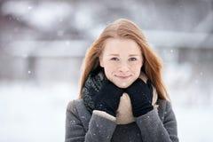 穿在被弄脏的冬天背景的秀丽画象自然看起来的年轻可爱的红头发人女孩被编织的围巾灰色外套 免版税库存照片