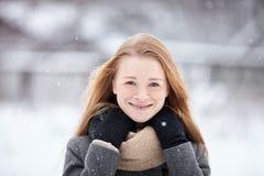 穿在被弄脏的冬天背景的秀丽画象自然看起来的年轻可爱的红头发人女孩被编织的围巾灰色外套 图库摄影
