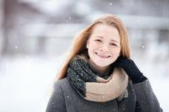 穿在被弄脏的冬天背景的秀丽画象自然看起来的年轻可爱的红头发人女孩被编织的围巾灰色外套 库存图片