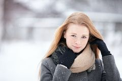 穿在被弄脏的冬天背景的秀丽画象自然看起来的年轻可爱的红头发人女孩被编织的围巾灰色外套 免版税库存图片