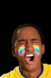穿在黑背景前面的特写深色皮肤的男性黄色橄榄球衬衣,下垂面部油漆,闭上的眼睛 免版税库存照片