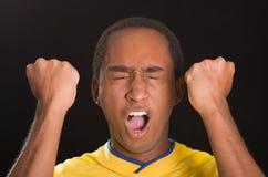 穿在黑背景前面的特写深色皮肤的男性黄色橄榄球衬衣,注视开放闭合和的嘴 免版税库存图片