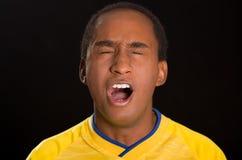 穿在黑背景前面的特写深色皮肤的男性黄色橄榄球衬衣,注视开放闭合和的嘴 图库摄影