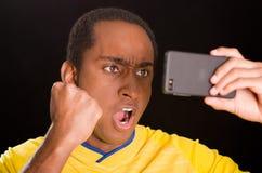 穿在黑背景前面的特写深色皮肤的男性黄色橄榄球衬衣,阻止手机观看 库存照片