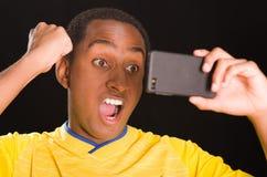 穿在黑背景前面的特写深色皮肤的男性黄色橄榄球衬衣,阻止手机观看 免版税库存图片