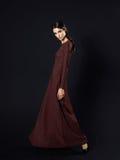 穿在黑背景的时装模特儿长的褐红的礼服 免版税库存图片