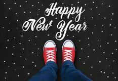 穿在黑背景的脚红色鞋子与新年快乐 免版税图库摄影