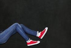 穿在黑背景的脚红色鞋子 免版税库存图片
