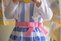 穿复活节礼服的小女孩拿着汁液玻璃 免版税库存图片