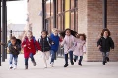 穿外套和运载书包的一个愉快的不同种族的小组年轻学校孩子运行在有他们的同学的o一个走道 图库摄影