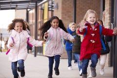 穿外套和运载书包的三个愉快的年轻学校女孩运行在有他们的同学的一个走道在他们的infa之外 免版税库存图片