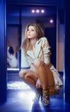 穿外套的白肤金发的妇女画象室内。摆在现代内部的外套的美丽的少妇。便装样式的妇女 库存图片