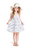 穿大白色帽子和礼服的微笑的小白肤金发的女孩 免版税库存图片