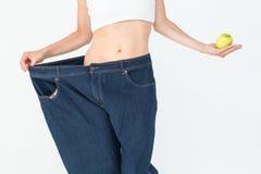 穿太大牛仔裤的亭亭玉立的妇女拿着苹果 库存图片
