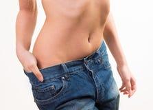 穿太大裤子的适合的妇女 免版税库存照片
