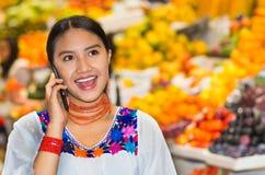 穿安地斯山的传统女衬衫的美丽的年轻西班牙妇女使用在水果市场里面的手机,五颜六色 库存照片