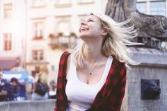 穿岩石红色衬衣,白色T恤的白肤金发的女孩生活方式画象 库存图片