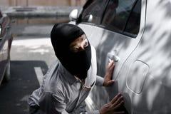 穿巴拉克拉法帽的被掩没的夜贼准备好对抢劫反对汽车背景 保险罪行概念 免版税库存图片