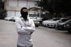穿巴拉克拉法帽的被掩没的夜贼准备好对抢劫反对汽车背景 保险罪行概念 免版税库存照片