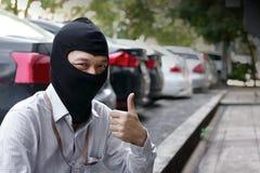 穿巴拉克拉法帽的被掩没的夜贼显示重击上升准备好对抢劫反对汽车背景 保险罪行概念 免版税库存图片